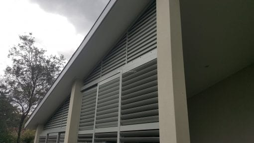 rivacy screen with sliding adjustable blades with a fixed blade above on a angle