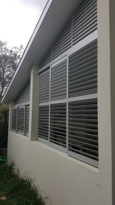 Privacy screen with sliding adjustable blades with a fixed blade above on a angle