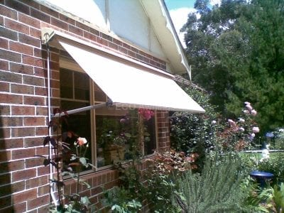 Pivot arm fabric awnings
